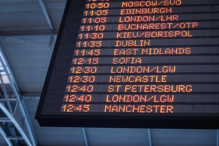 A low-angle shot of an airport departure screen.